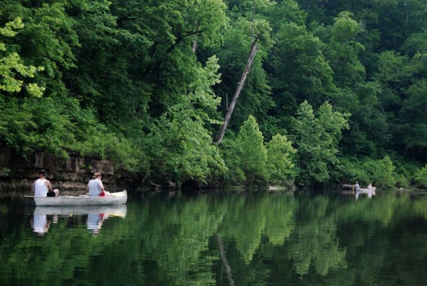 Photograph of people in a canoe fishing at one of the many pools on Jacks Fork river, the Ozark National Scenic Riverway.