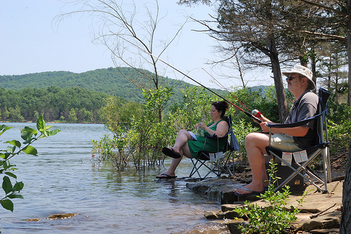 A man and woman relax and fish while sitting on the shore of Table Rock Lake at Big Bay Recreation Area.