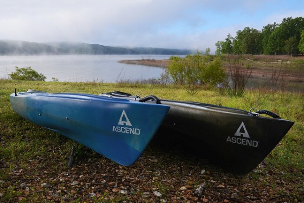 Blue Ascend D10 and Camo Ascend FS10 kayaks are pulled ashore on a foggy morning at Truman Lake.