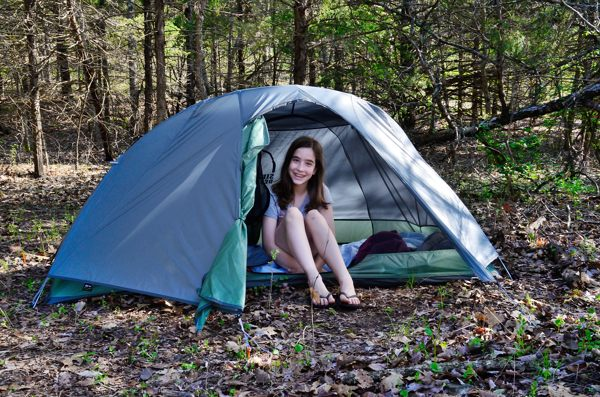 Smiling teen girl sitting in a Sierra Designs Lightning XT1 Tent during her first backpacking trip. At Piney Creek Wilderness in Barry County.