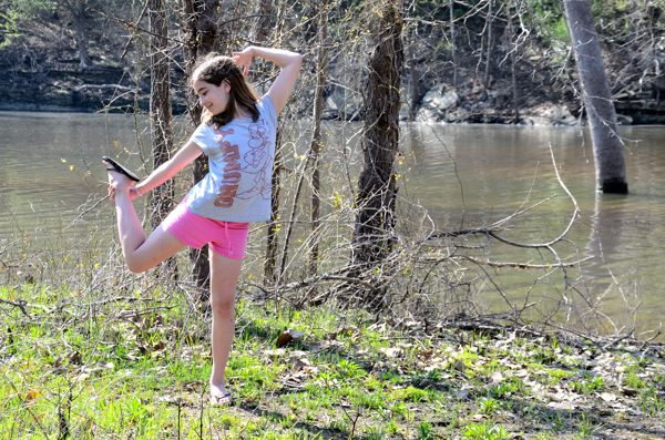 Teen girl being silly alongside Piney Creek near Table Rock Lake during a spring backpacking trip.