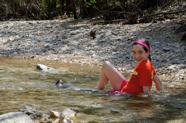 Teen girl sitting in cool creek water on a hot day during a spring backpacking trip to Piney Creek Wilderness in Barry Count, Missouri.