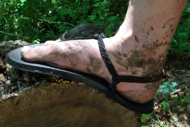 A muddy foot in a pair of home-made hiking huaraches