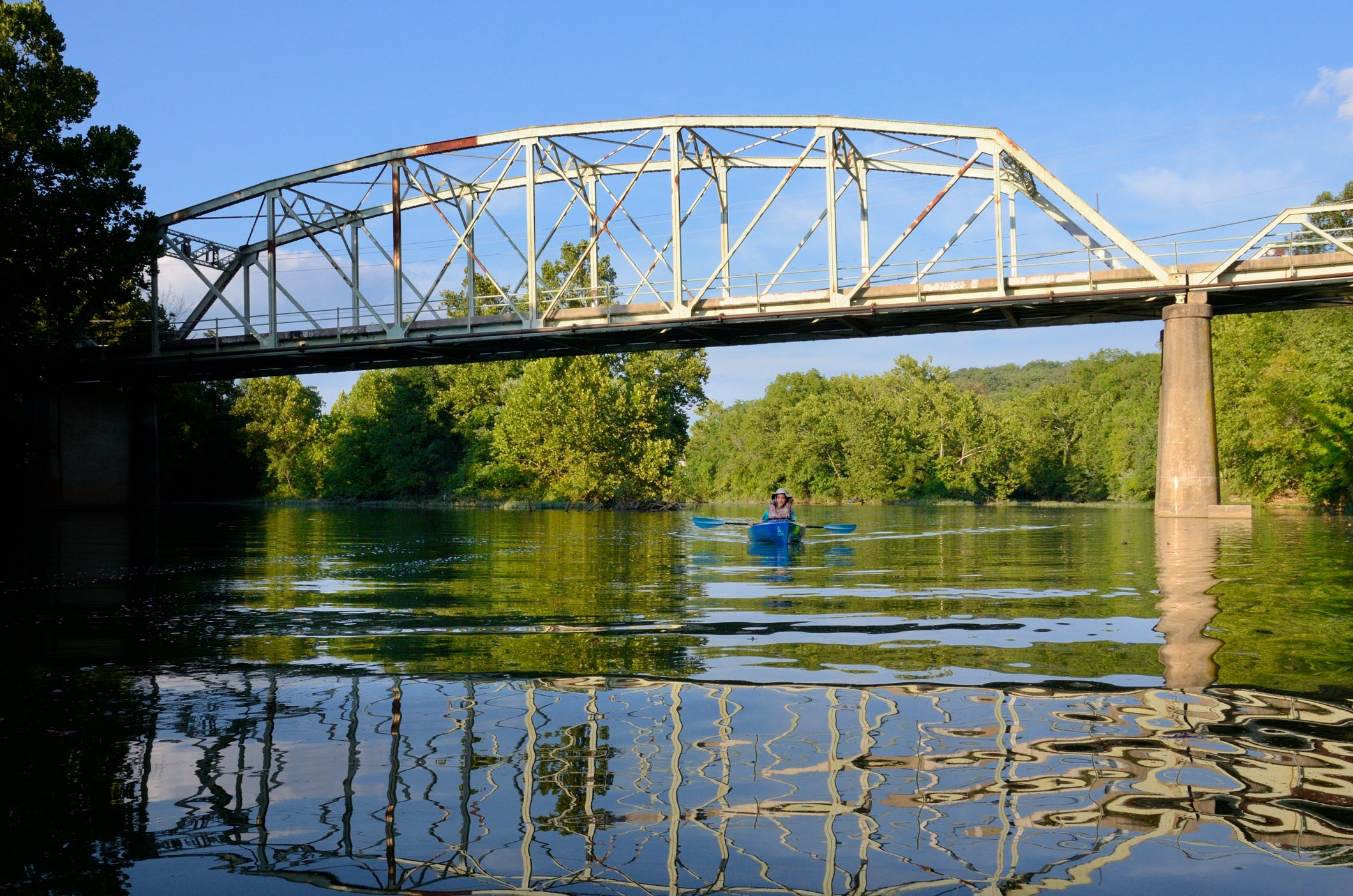 aA kayak passing under the old bridge, a part of the Galloway Creek Greenway and James River trail